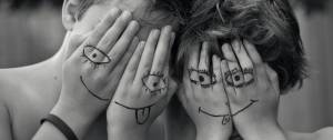 Deux enfants qui se cachent le visage avec leurs mains. Ils ont dessiné des smileys