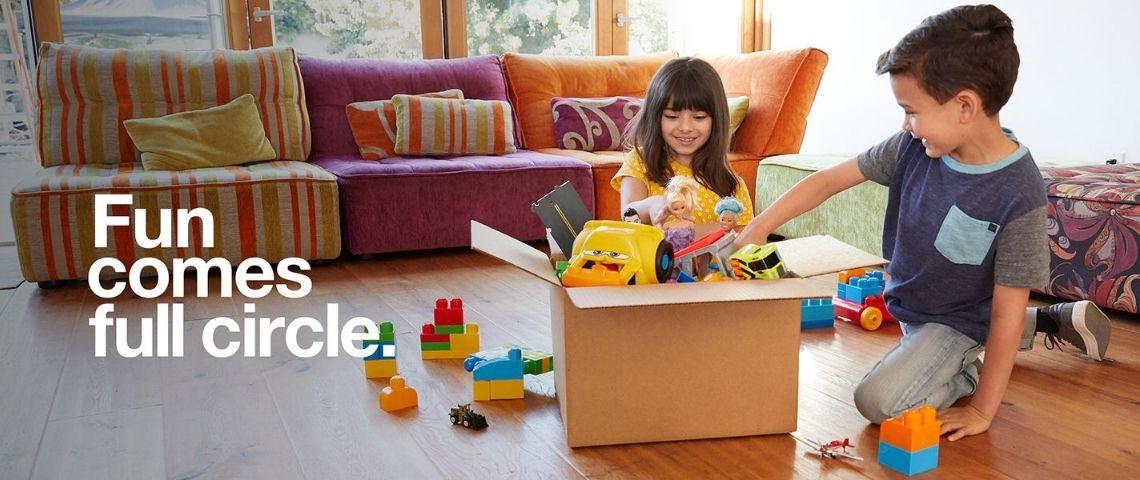 Des enfants qui mettent des jouets dans un carton