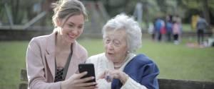 Jeune femme et personne âgées sur un banc avec un smartphone