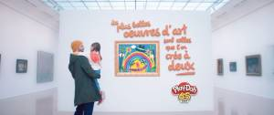 Papa tenant un enfant dans ses bras dans un musée, devant un tableau