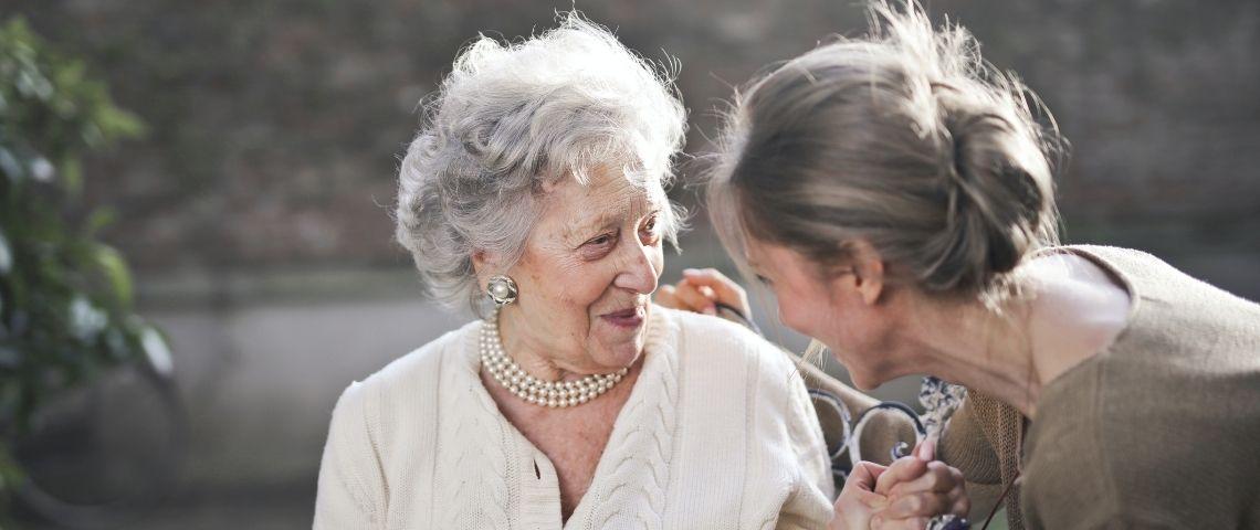 Femme tenant la main d'une personne âgée