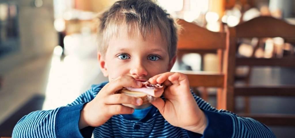 un enfant qui mange du jambon