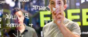 Un homme qui écrit sur un tableau transparent avec un autre homme derrière lui qui regarde