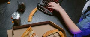 Main sur un clavier d'ordinateur, avec un verre de soda et une pizza entâmée posées à côté