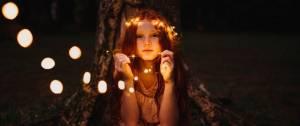 enfant avec une guirlande lumineuse en couronne autour de la tête