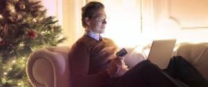 Homme sur un canapé, avec une carte bancaire à la main, devant un ordinateur