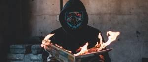 Homme masqué lisant un journal qui prend feu