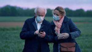 Personne âgée avec un smartphone accompagnée d'une femme