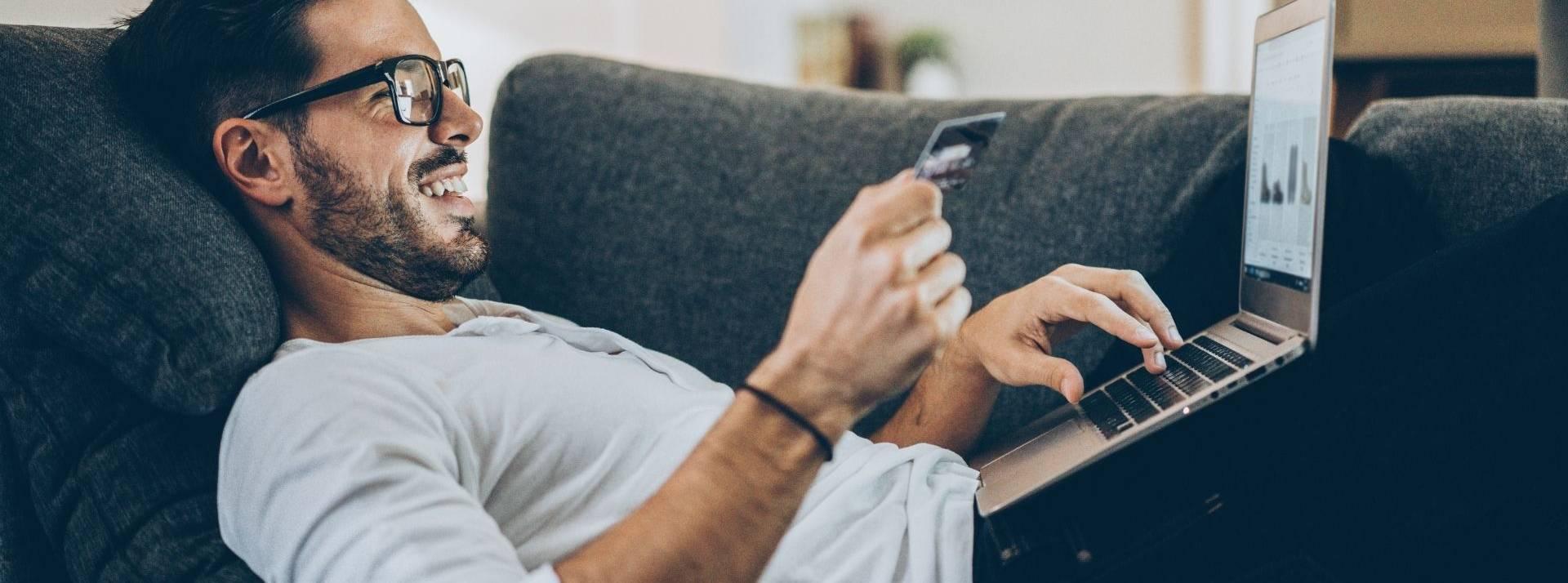 Homme allongé sur un canapé devant un oridinateur avec une carte bancaire dans la main