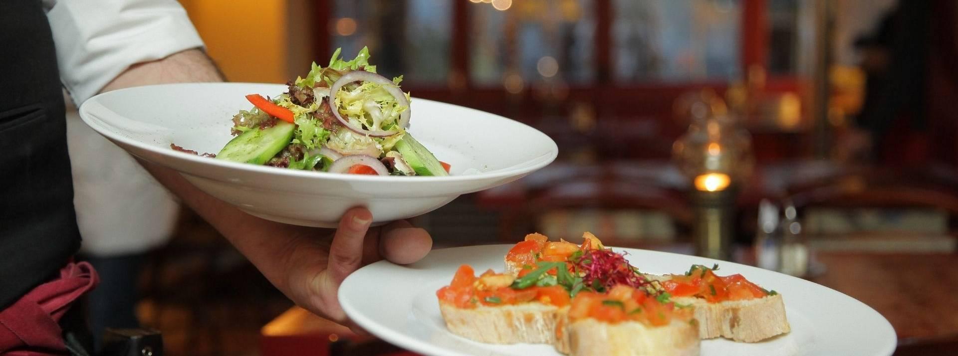 Serveur avec 2 assiettes dans la main