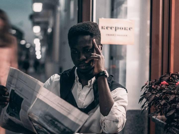 Homme lisant un journal dans un bar