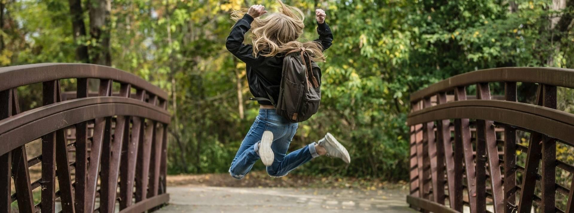 Jeune fille de dos sautantde joie
