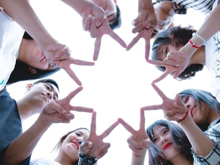 Groupe de personnes formant une étoile à l'aide de leurs mains
