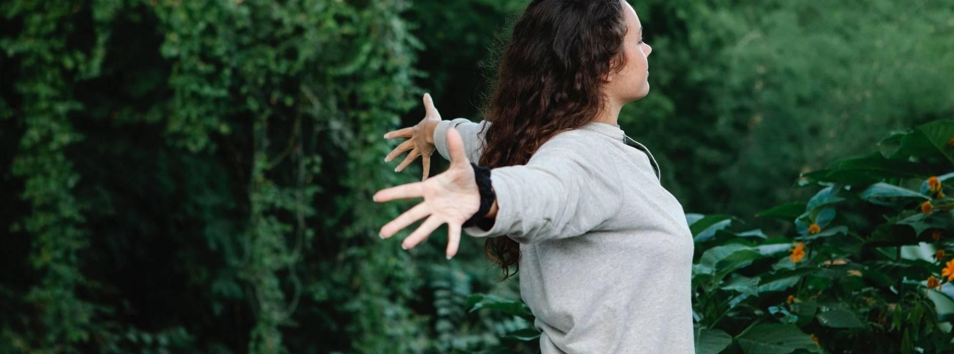 Jeune femme écratrant les bras entourée d'arbre