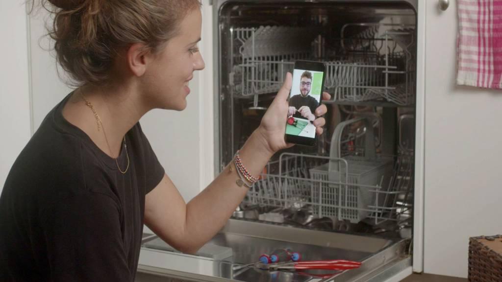 Femme avec un smartphone devant un lave-vaisselle