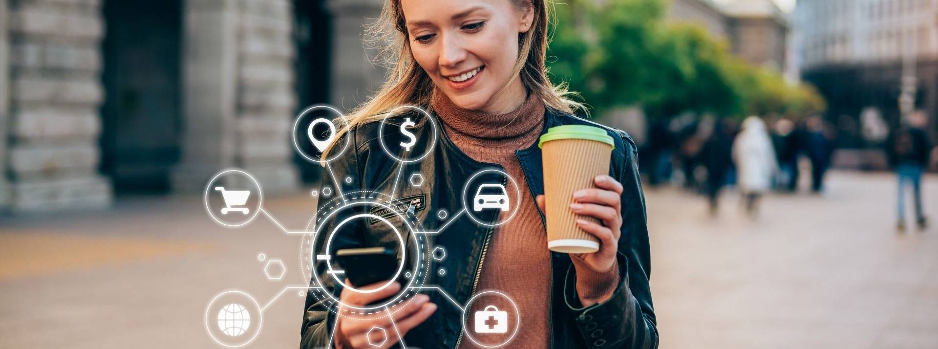 Jeune femme avec un smartphone dans la main droite et un mug dans la main gauche