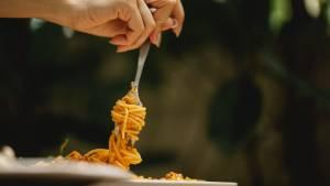 Femme tenant une fourchette avec des pâtes