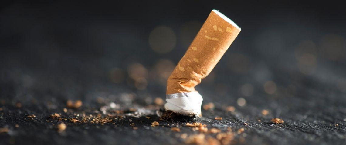 Mégot de cigarette écrasée sur le sol.