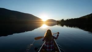 Femme sur une barque au soleil couchant