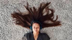 femme allongée sur de la moquette écoutant de la musique