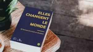 """Livre """"Elles changent le monde"""" posé sur une table basse en bois"""