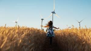 Petite fille dans un champ de blé avec des éoliennes