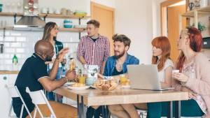 Groupe de personnes prenant le petit déjeuner autours d'une table dans un appartement